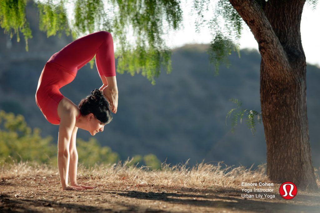 Woman in nature doing scorpion yoga pose in red athletic wear.
