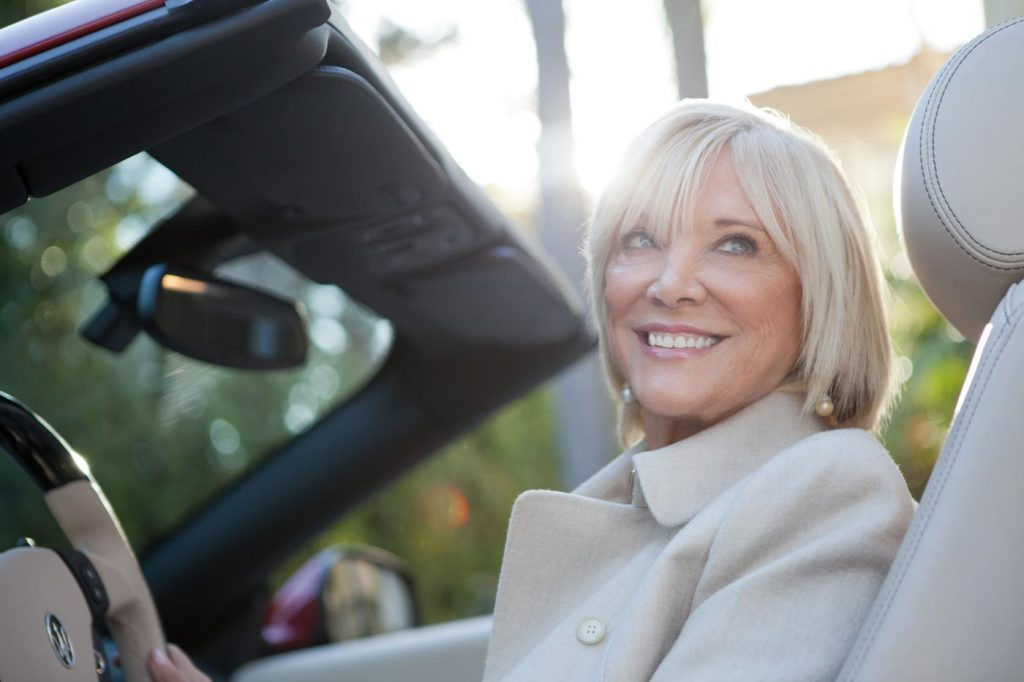 A portrait of Betty Graham for Coldwell Banker Previews, a classy older lady with silver hair smiling off camera sitting in the driver seat of a Maserati. Photo taken by Los Angeles corporate photographer Nick Reid.