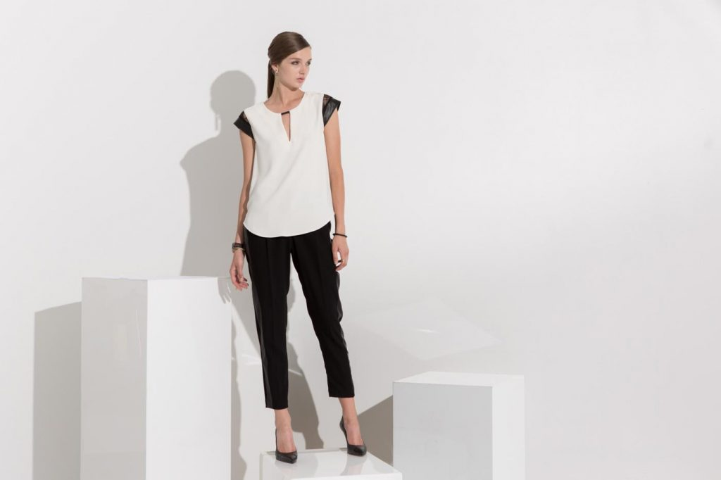 Women's fashion campaign photo of a model in a black and white outfit on white boxes.