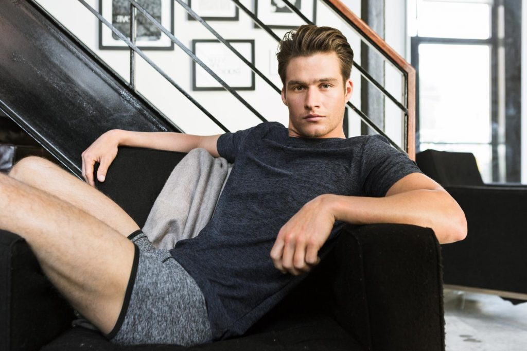A Lifestyle photograph by product photographer Nick Reid of a man sitting comfortably in a black chair wearing a shirt and boxer briefs.