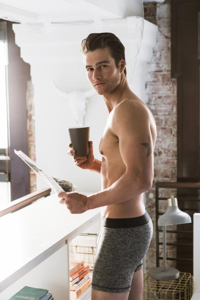 Lifestyle photograph by fashion photographer Nick Reid of a man in his boxer briefs having a coffee and reading the paper in his Los Angeles loft.