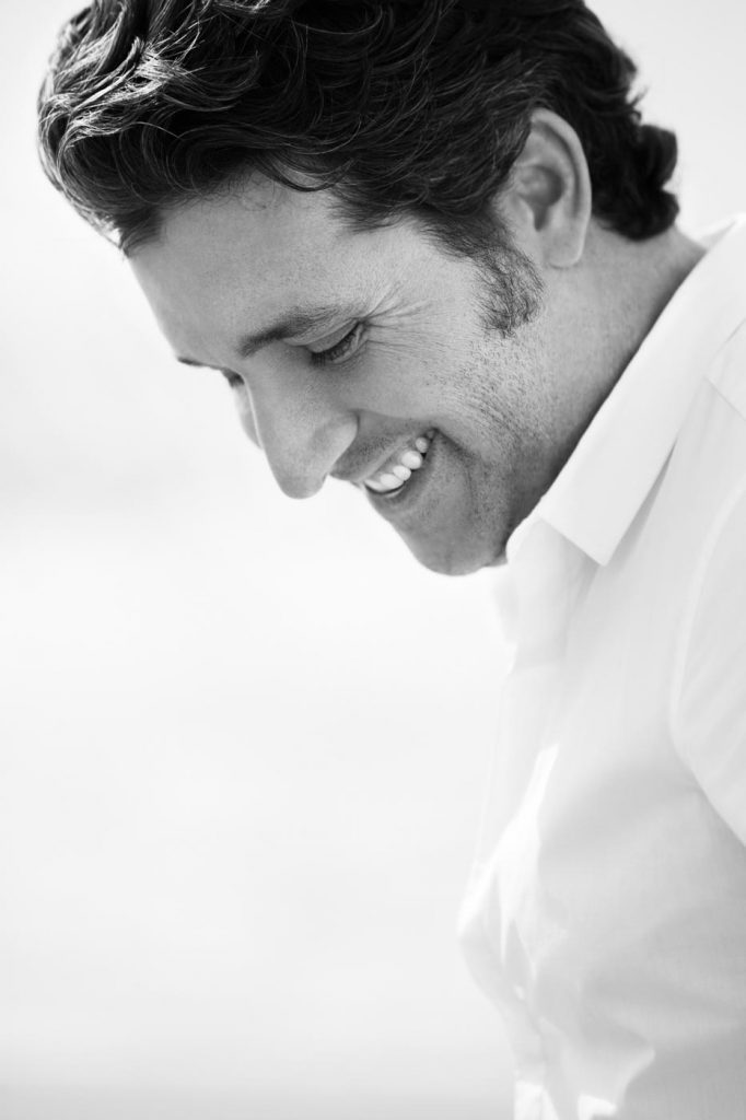 A black and white profile portrait of Chris Cortazzo smiling. Portrait taken by corporate photographer Nick Reid