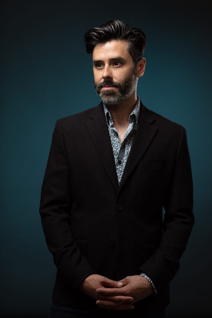 Portrait of a bearded middle age while man wearing a suit jacket on a blue background by corporate portrait photographer Nick Reid.