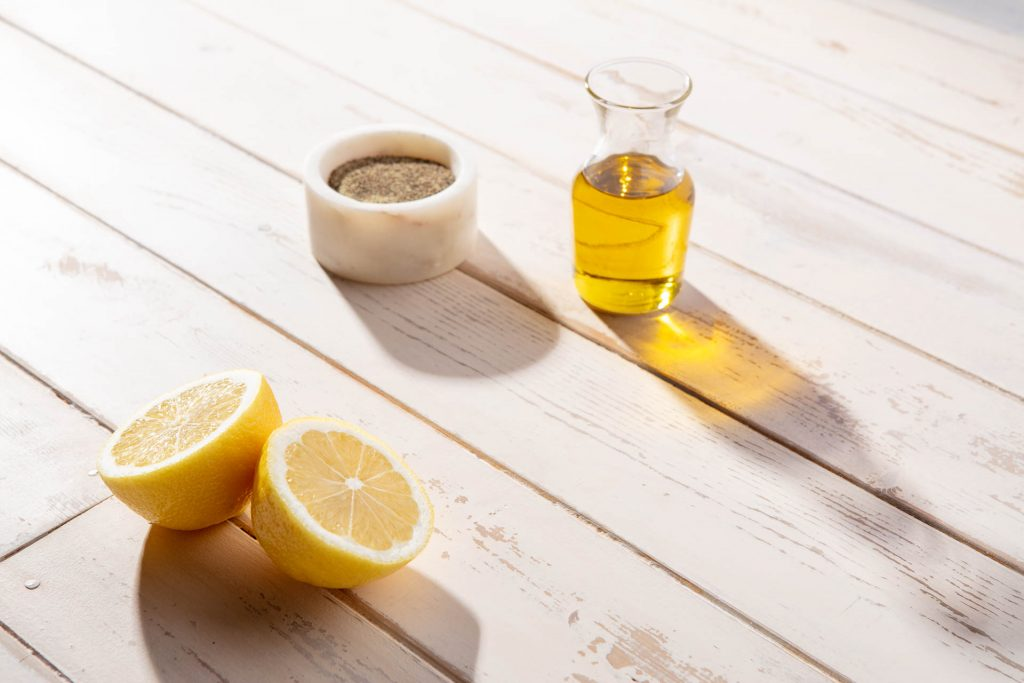 A sliced lemon, bowl of pepper and carafe of olive oil on a white wooden table in the morning light.
