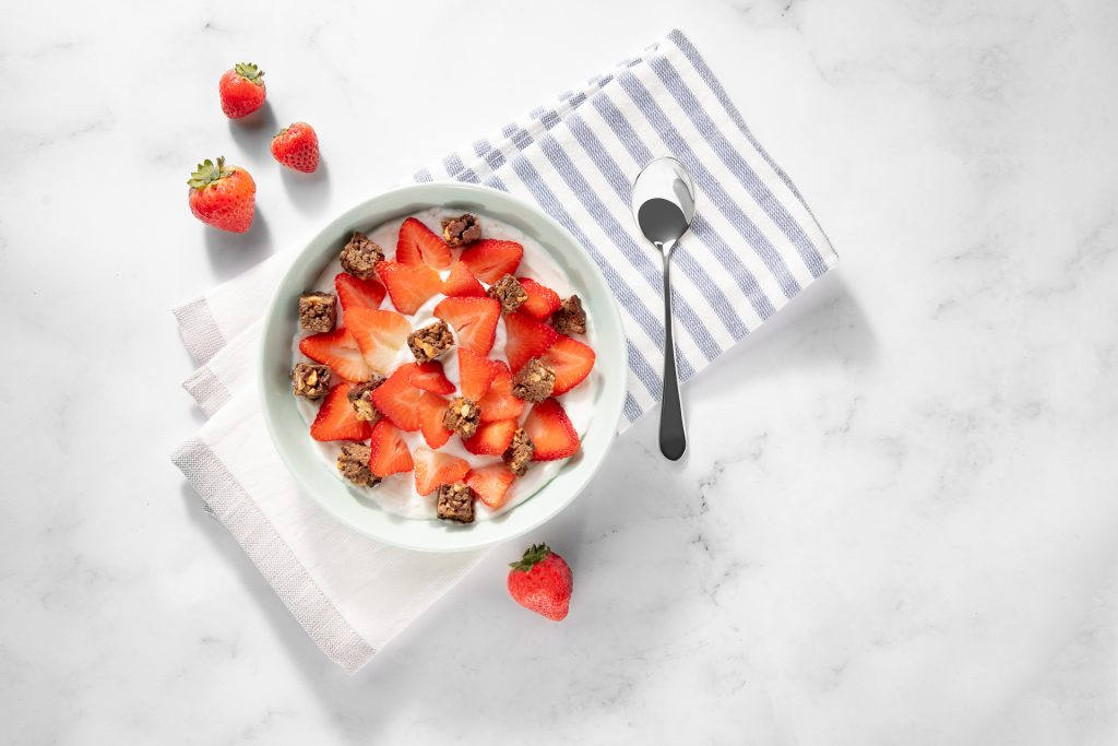 over head shot of strawberries and breakfast bars bites in a bowl on a striped napkin on marble countertop..